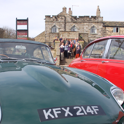 Two vintage jaguar cars with a group of people standing outside the Norfolk Arms in the background.