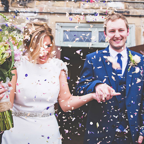 A newly married couple being showered with confetti - photographed by John Anderson Photography