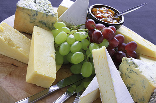 A selection of cheeses and grapes on a board