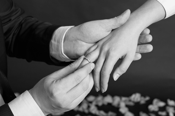 A close-up of a man's hand placing a wedding ring on a woman's finger