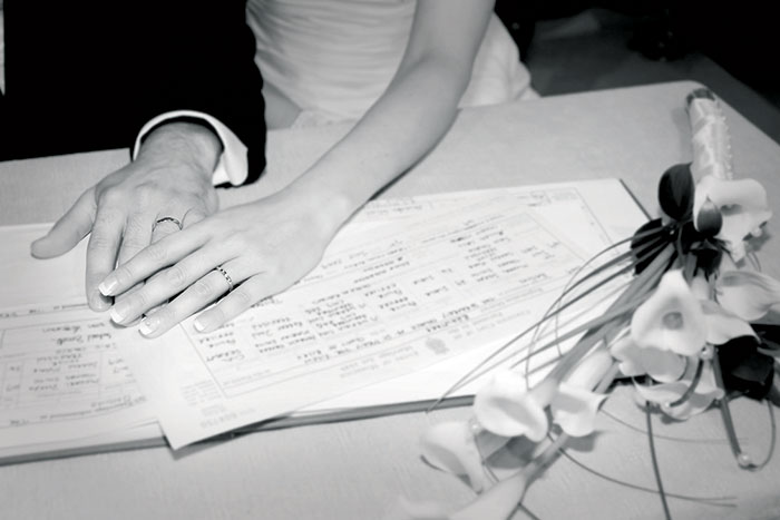 A couple's hands showing their rings after signing the register