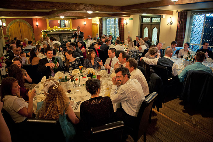 The Mayfield Room during a wedding reception with guests sitting at tables, laughing and eating